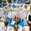 Dani Sinclair crouches in front of several players on the University of Victoria women's basketball team during a timeout. Several players also stand behind her.